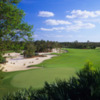 A view of green and fairway with sand traps on the left side at Calusa Pines Golf Club