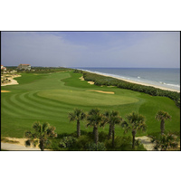 Hammock Beach Resort's Ocean Course finishes with a challenging par 4. The green is flanked with grass hollows on the right and a bunker and dune to the left.